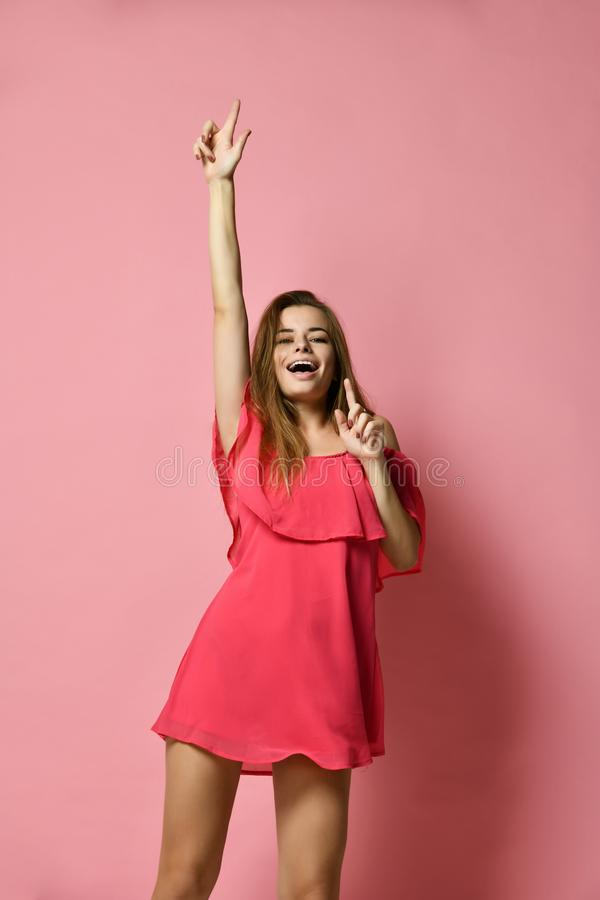 Young beautiful girl in a light summer pink dress dancing in your pleasure in the studio. royalty free stock photography