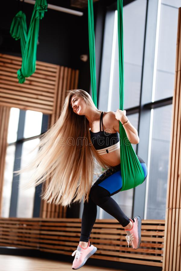 Young beautiful girl with long blond hair dressed in the sport clothes is doing fitness on the green aerial silk in the stock image