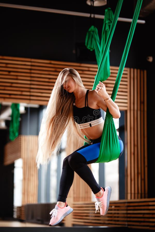 Young beautiful girl with long blond hair dressed in the sport clothes is doing fitness on the green aerial silk in the royalty free stock photo