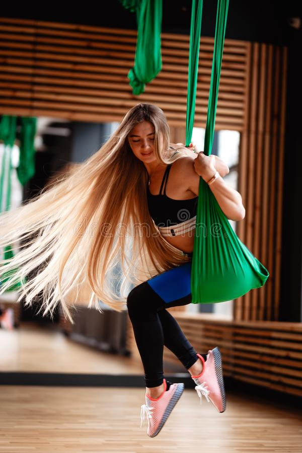 Young beautiful girl with long blond hair dressed in the sport clothes is doing fitness on the green aerial silk in the stock photo
