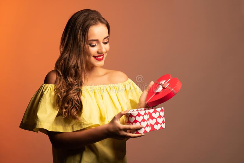 Young beautiful girl in yellow dress which holds a gift and looks at it. Orange background. Studio shot. Text stock photo