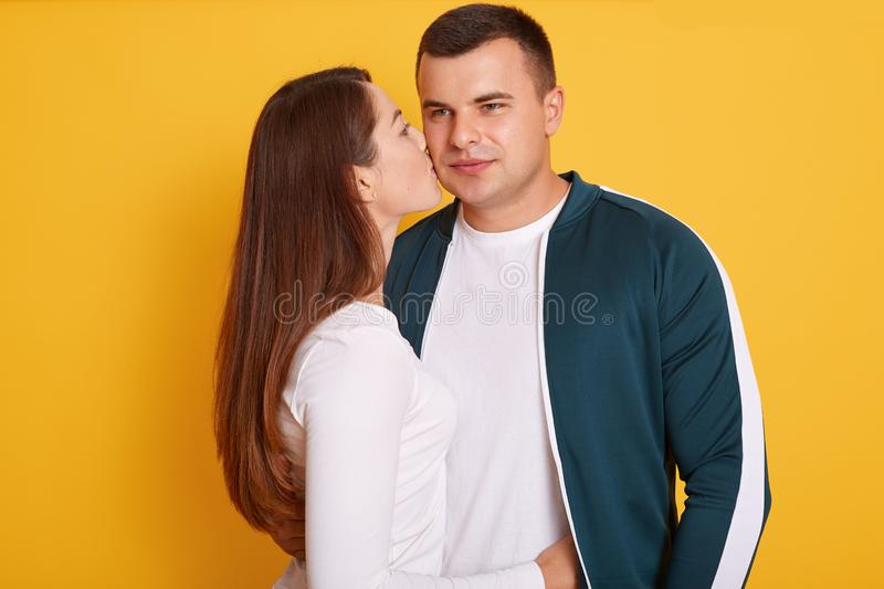 Young beautiful girl with long dark hair kissing her handsome boyfriend to cheek, posing in studio over yellow background, couple stock photos