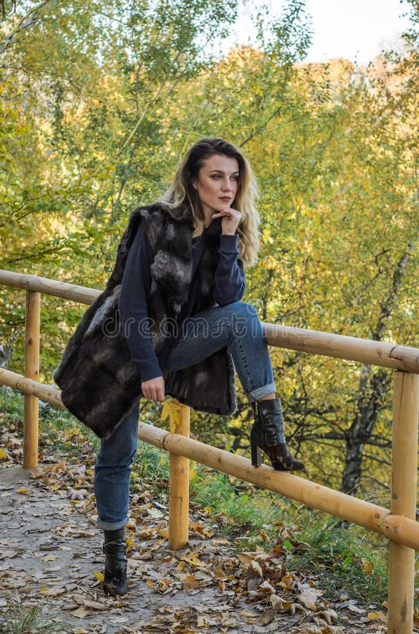Young beautiful girl with long hair, in a fur jacket, stands on a wooden railing on a bright sunny day while walking in the autumn royalty free stock photo