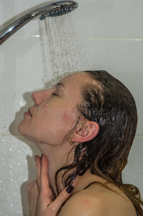 Young beautiful girl with long hair, naked, taking a shower and washing her head royalty free stock photography