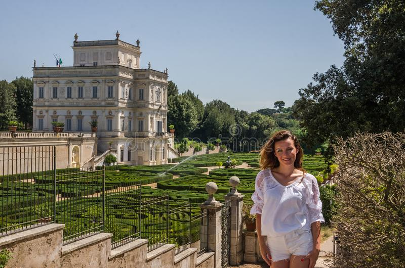 Young beautiful girl with long hair in a park at the villa Pamphili posed by a labyrinth of flowers and plants royalty free stock photography