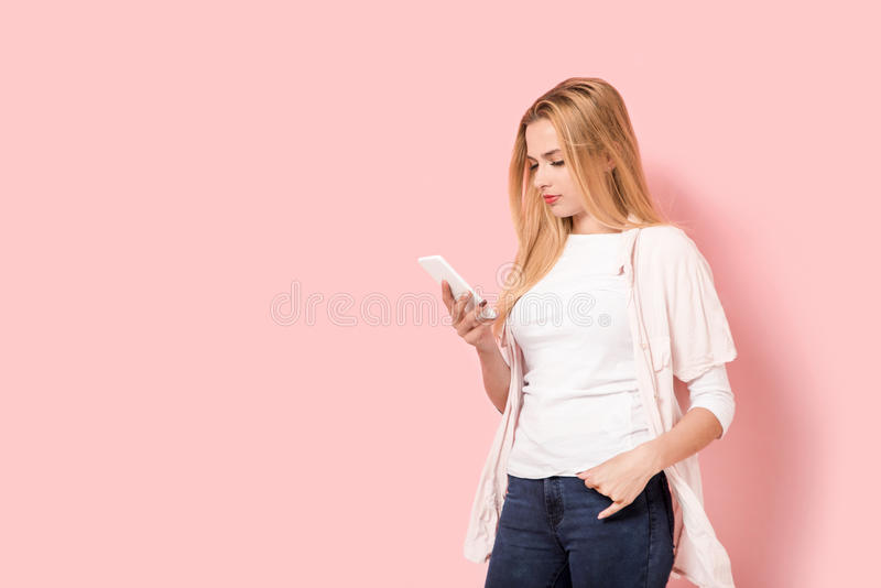 Young beautiful girl is looking at smartphone royalty free stock images