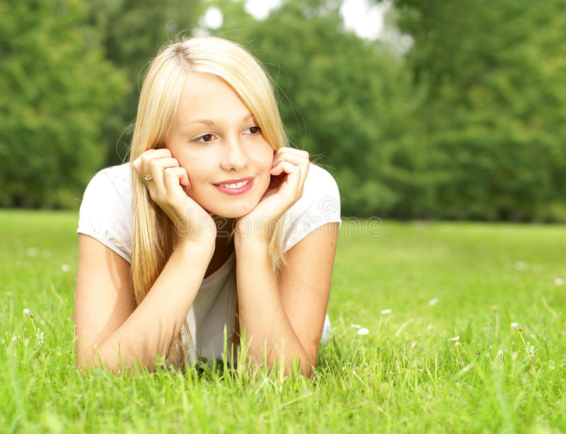 A Young And Beautiful Girl Is Lying On The Grass Stock Photos