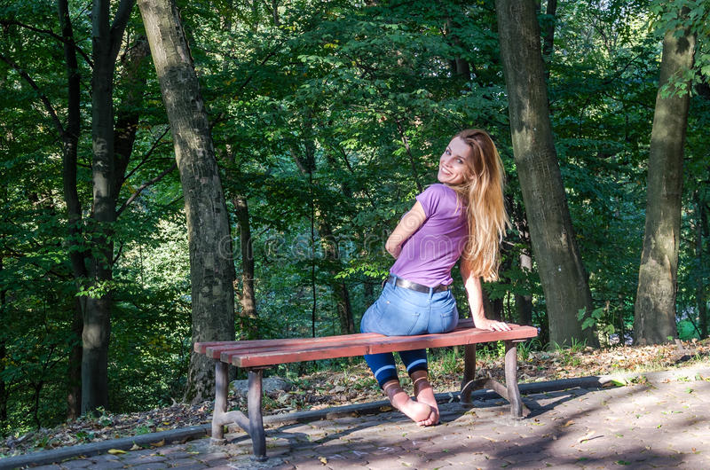 Young beautiful girl model in jeans and a T-shirt with long blond hair and sad smiles pensively posing for a walk in the autumn pa. Rk sitting on a bench among stock image