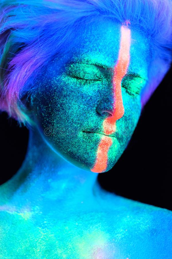 Model young beautiful girl portrait in studio with creative makeup, in neon ultraviolet lamp. Glows in the dark. Hair. Young beautiful girl model with short stock photo