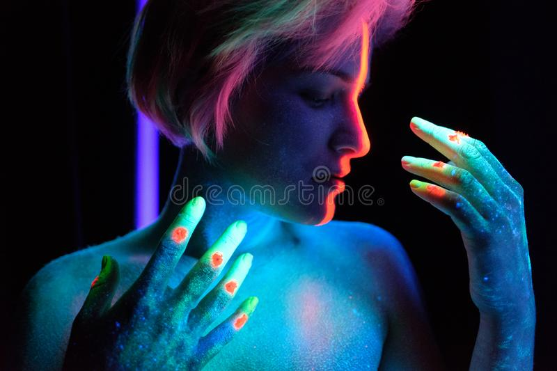 Model young beautiful girl portrait in studio with creative makeup, in neon ultraviolet lamp. Glows in the dark. Hair. Young beautiful girl model with short royalty free stock photography