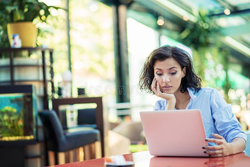 Young and beautiful girl with notebook and laptop sitting in a cafe stock photography