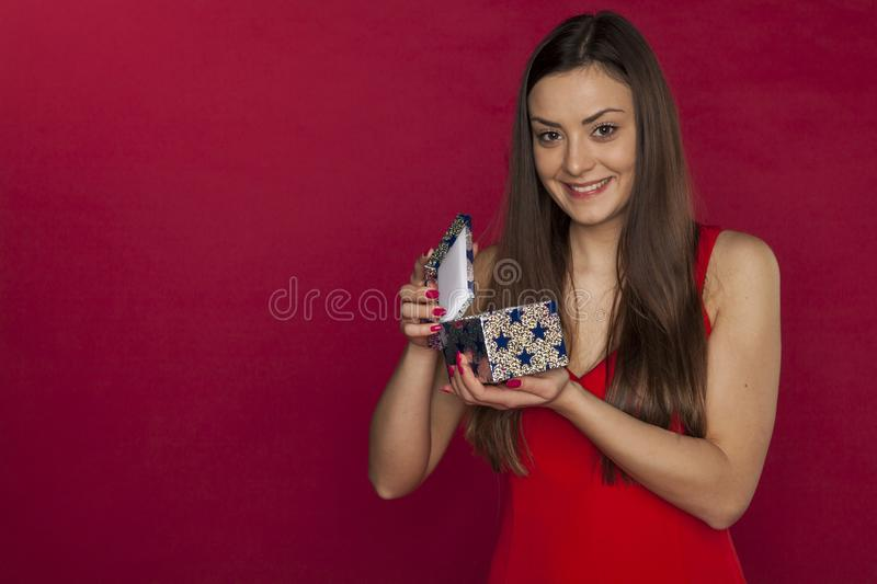 Young beautiful girl opens a magical Christmas gift royalty free stock image