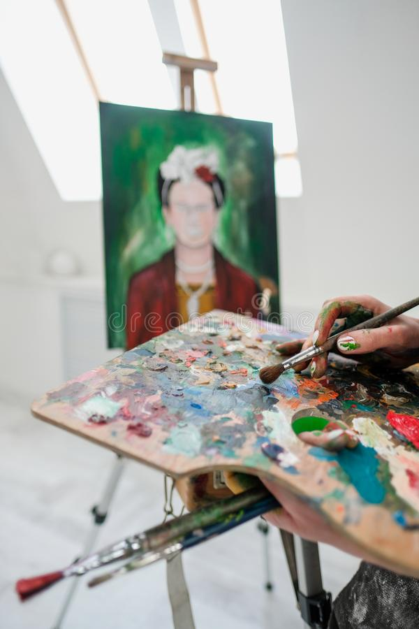 Young beautiful girl painter in a white studio draws on an easel on canvas. stock image