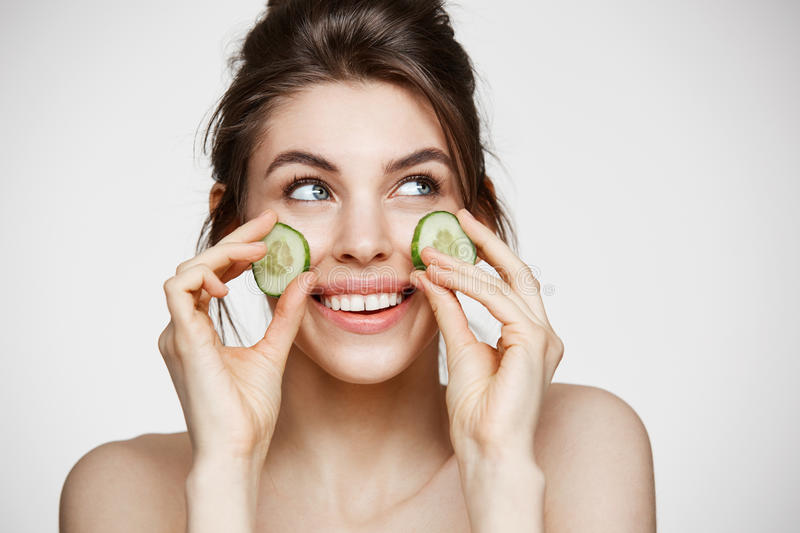 Young beautiful girl with perfect clean skin smiling holding cucumber slices over white background. Beauty cosmetology royalty free stock images