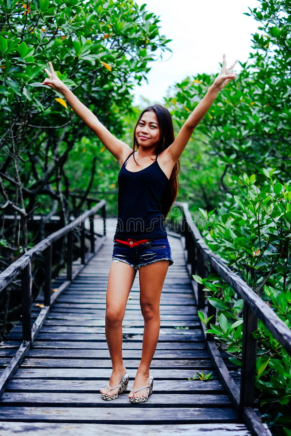 Young beautiful girl portrait on the wooden bridge in the mangrove forest.  stock photo