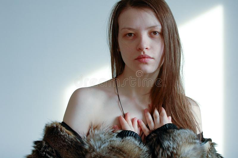 Young beautiful girl posing for a photographer and flirting with him, showing him some of her cute young body. Jacket of wolf fur.  stock image