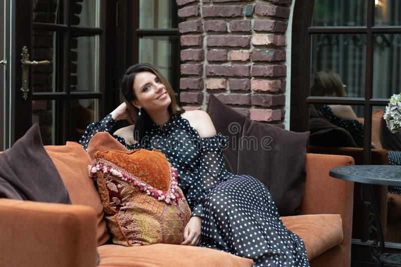Young beautiful girl posing on a sofa sitting outside royalty free stock image