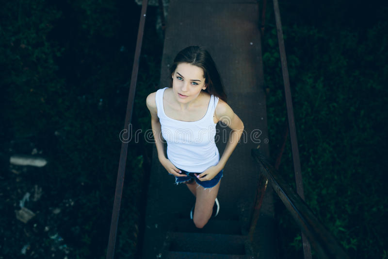 Young beautiful girl posing. While standing in an abandoned structure stock photo