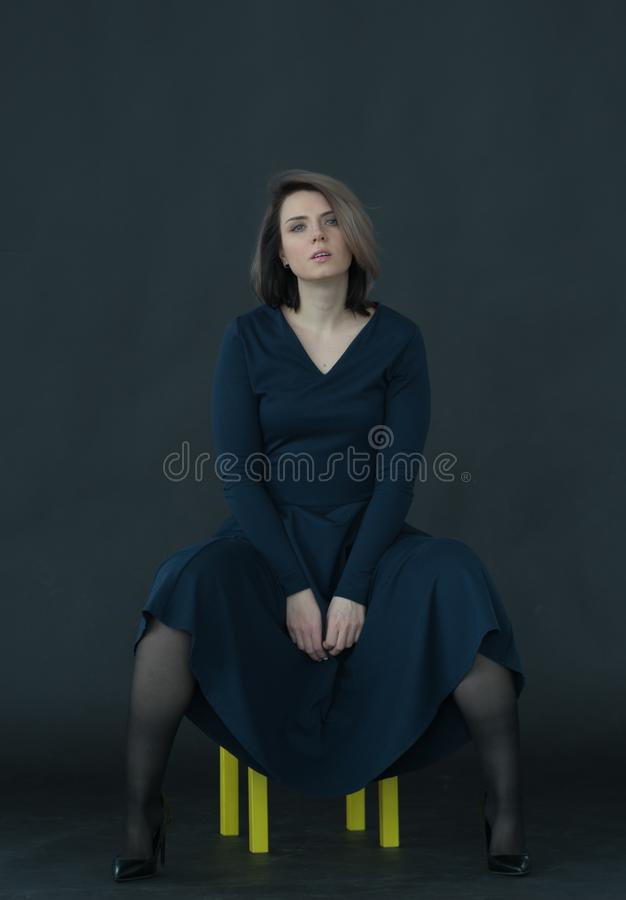 Young beautiful girl posing in studio, sitting on yellow chair. In blue dress stock photo