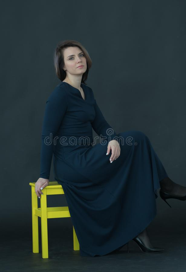 Young beautiful girl posing in studio, sitting on yellow chair. In blue dress stock image