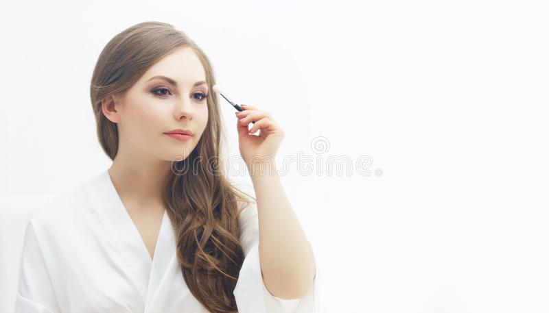 Beauty portrait of young and attractive girl. Make-up and cosmetics concept. Young and beautiful girl preparing makeup. Bride doing make-up near the mirror royalty free stock photography
