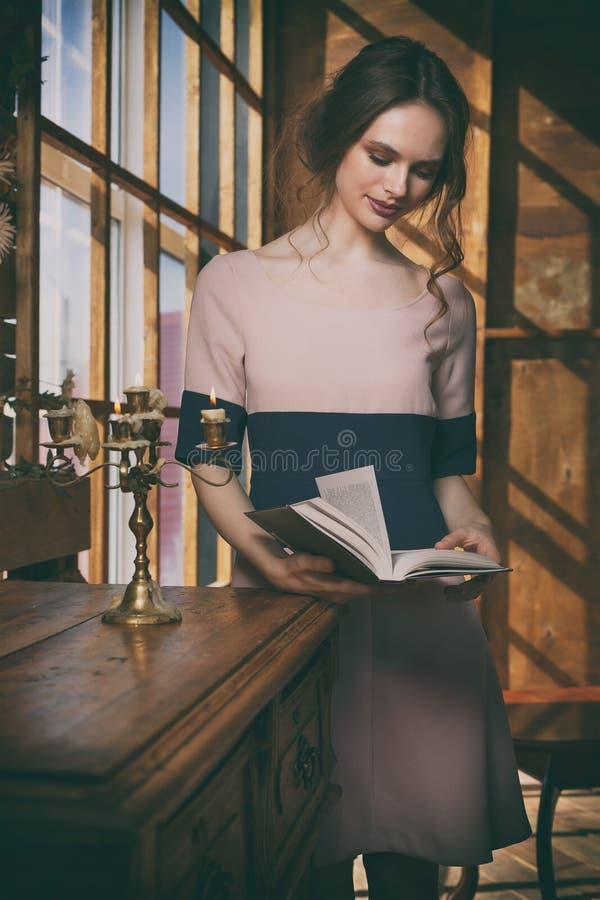 Young beautiful girl reads book near window stock image