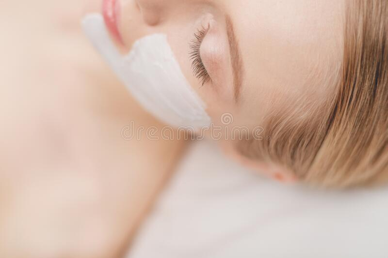 Young beautiful girl receiving pink facial mask in spa beauty salon stock images