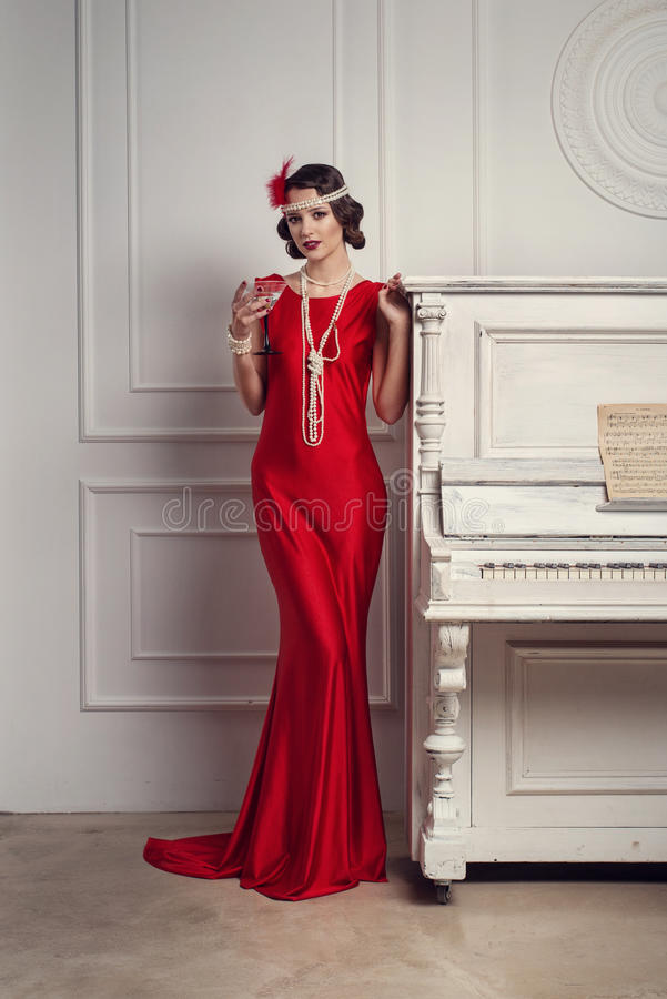 Young beautiful girl in red dress style of the 20`s or 30`s with glass of martini near the piano. Vintage style beautiful woman. stock images