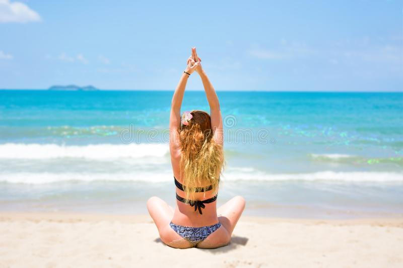 A young, beautiful girl with red hair, in a bikini. practices yoga on the white sand and turquoise sea. stock photos