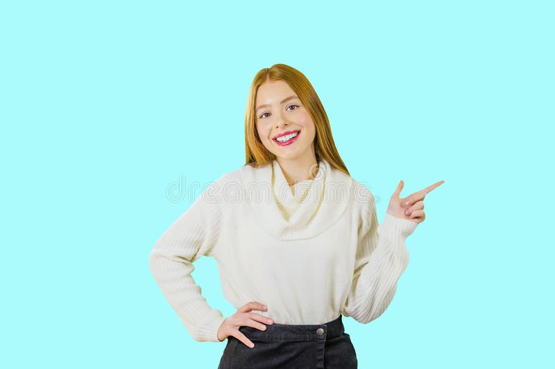 Young beautiful girl with red hair with her head bent to the side with her index finger pointing to the side and smiling stock photography