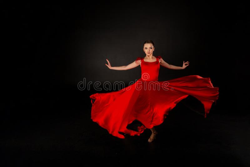Young beautiful girl in red waving flying dress stock photos