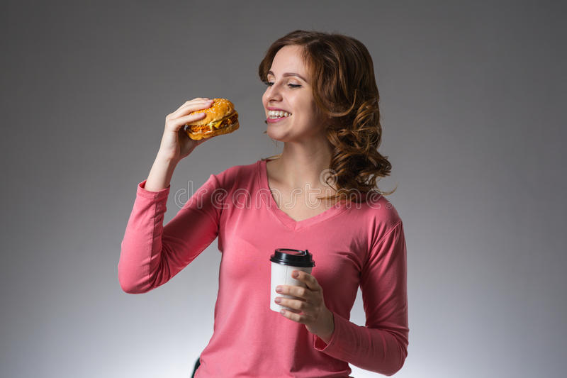Young beautiful girl with a sandwich and a cup of coffee from a royalty free stock photo