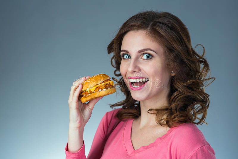 Young beautiful girl with a sandwich from a fast food stock photo