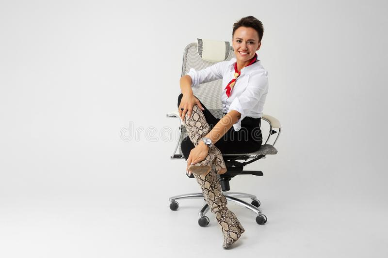 A young beautiful girl with short dark hair, makeup in a white shirt, black pants, long leather snake boots, with a red stock photography