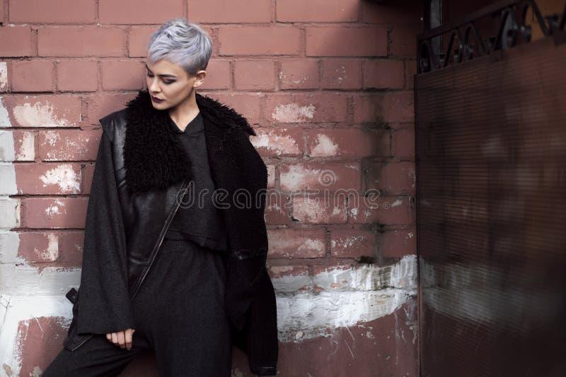 Young beautiful fashion girl shooting outdoors near brick wall at home royalty free stock image