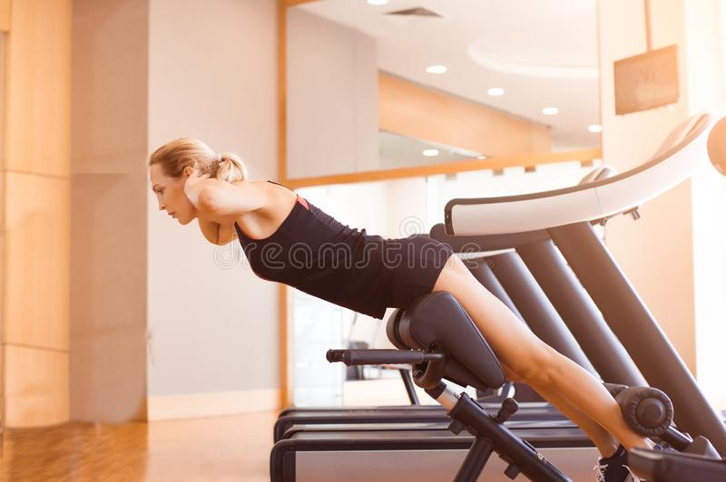 Young beautiful girl in short sport shorts and a black sleeveless jersey engaged in fitness in the gym stock photo