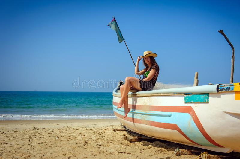 Young beautiful girl in short transparent dress and straw hat sits on a wooden fishing boat against blue sea on hot tropical day. The Beaches Of Goa, India stock images