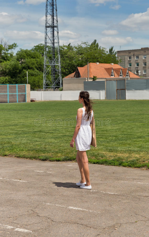 Young beautiful girl in short white dress with windswept hair. Young beautiful caucasian girl in a short white dress with windswept hair walk along a treadmill stock photos