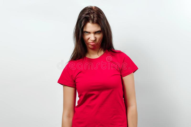 Young, beautiful girl, shows an emotion of disappointment, sadness, apathy. Isolated on a light background. Different human. Emotions, feelings of facial stock photography