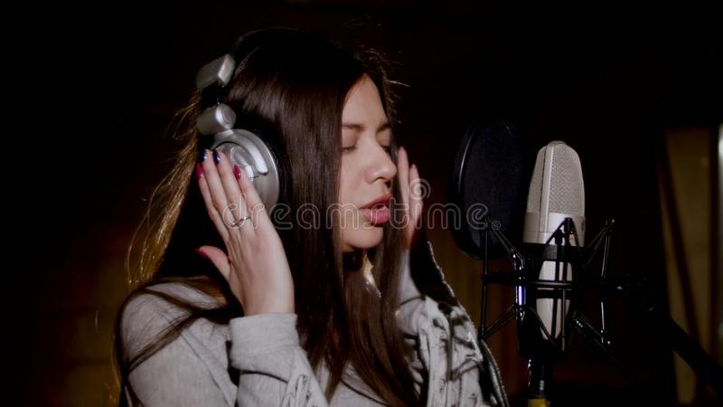 Young beautiful girl sings.Young singer singing into a microphone.Portrait close up of the singer.Recording studio royalty free stock images