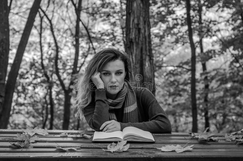 Young beautiful girl sitting in autumn park behind a wooden table reading a book stock photos