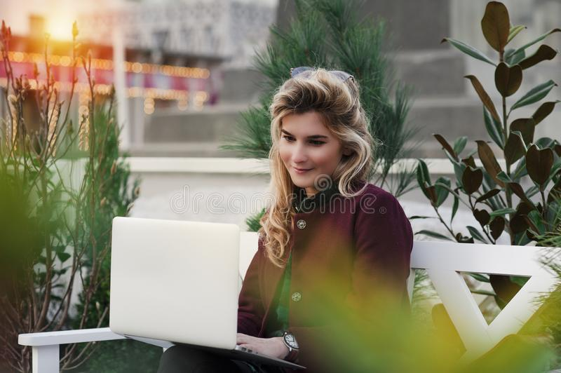 Beautiful girl is sitting on a bench with a laptop in her hands on a fresh street with the city. A concept work in pleasure, royalty free stock photo