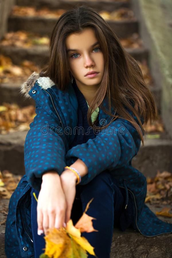 Young girl sitting on the stone steps in autumn park background royalty free stock photo