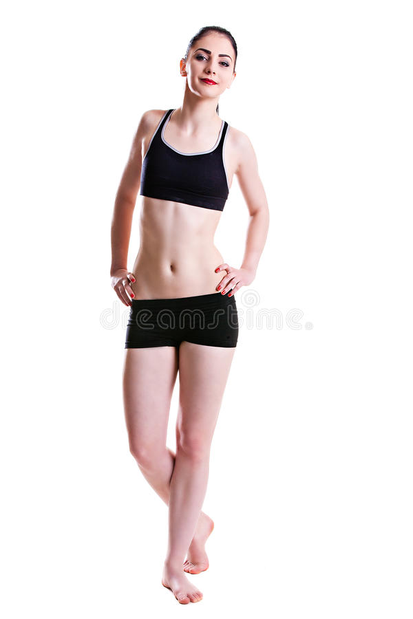 Young beautiful girl with a smile in fitness clothes. Beautiful young sport, smiling brunette in black fitness clothes royalty free stock photography