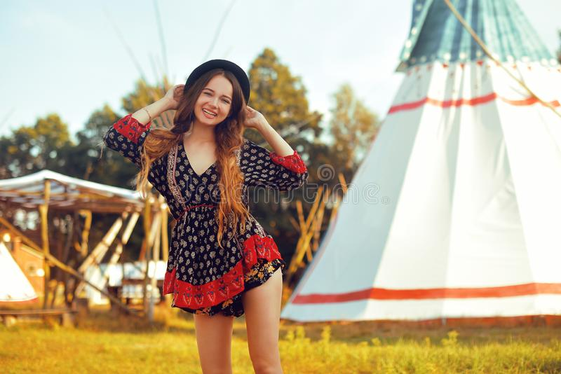 Young beautiful girl smiling on background teepee, tipi- native indian house. Pretty girl in hat with long cerly hair stock photography