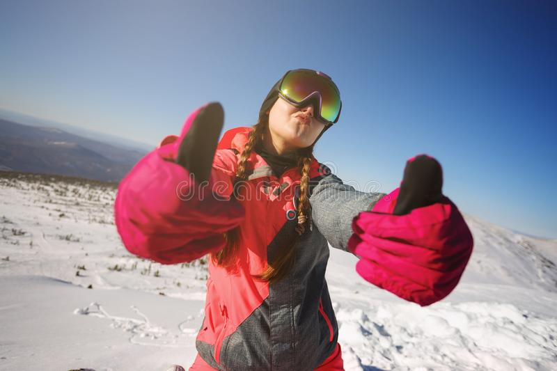 Young beautiful girl snowboarder with mask on her face holds thumbs up. Sheregesh Russia stock photo