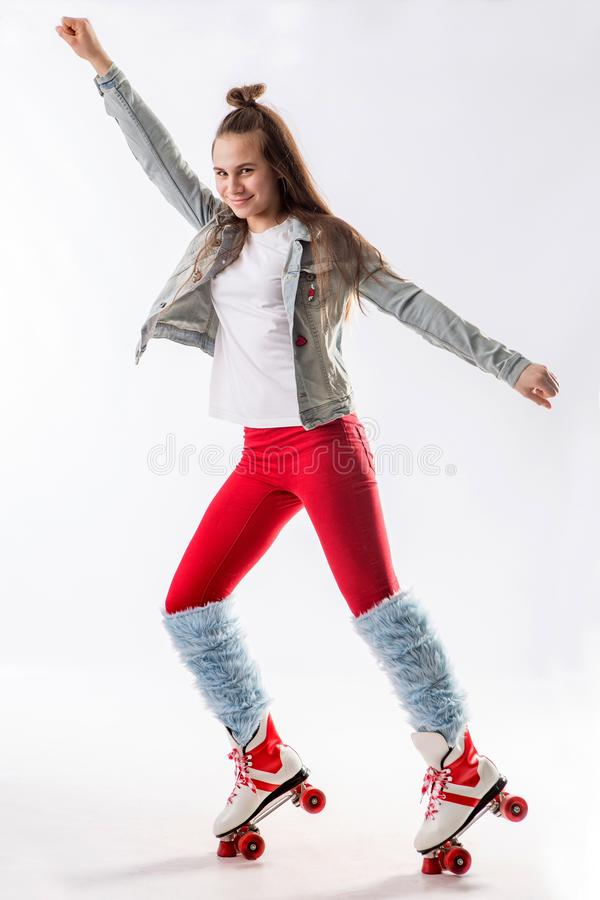 Young beautiful girl in sporty stylish clothes with long hair on four-wheeled rollers isolated on background stock photo