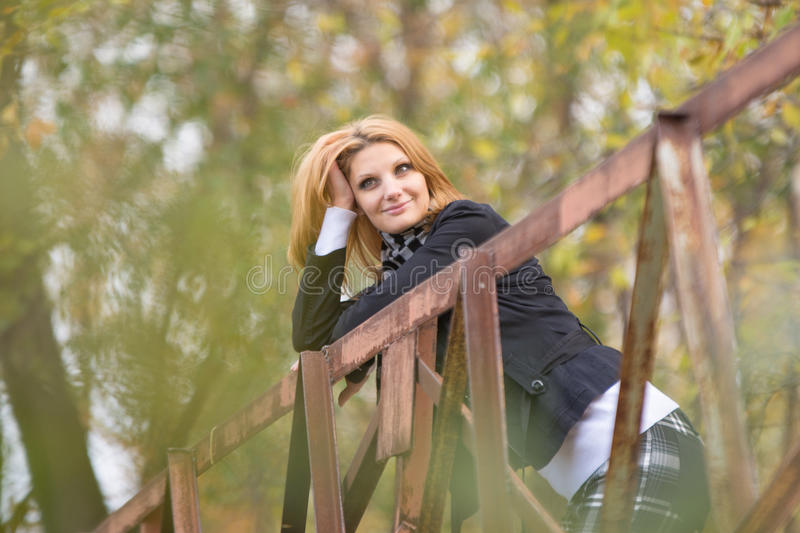 Young beautiful girl standing on the bridge, leaning on the railing and looking pensively into the distance. Young beautiful girl stands in the forest Bridge in royalty free stock image