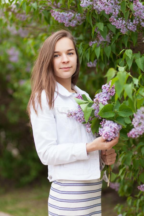 Young beautiful girl stands near the bushes of blooming lilac stock image