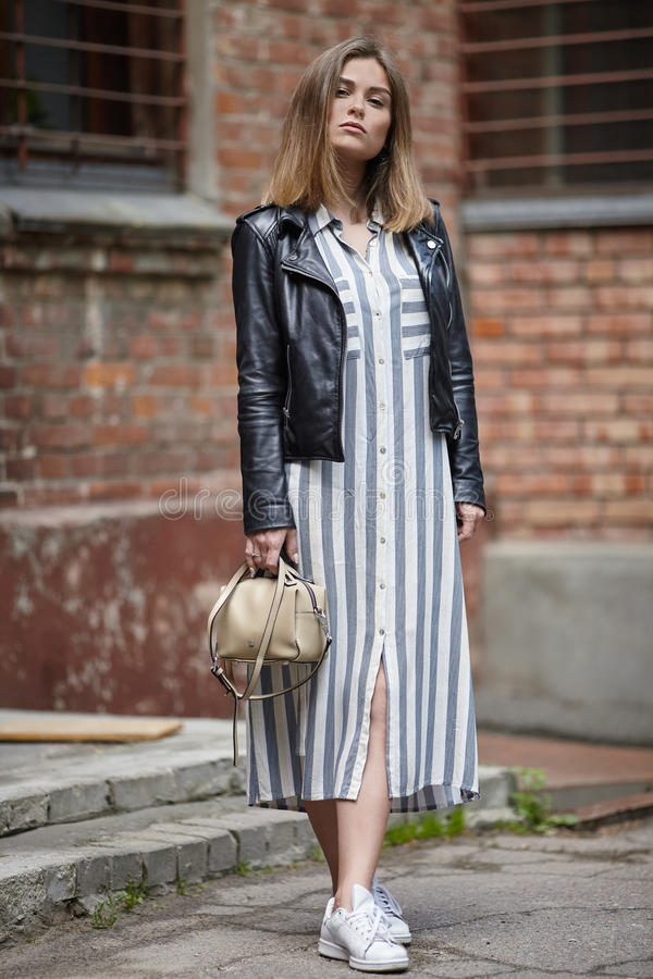 Young beautiful girl in stylish streetwear black leather jacket long striped dress white sneakers and with a fashionable bag posin. G against brick wall royalty free stock image